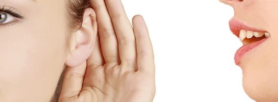 Una ragazza parla all'orecchio di un'altra ragazza