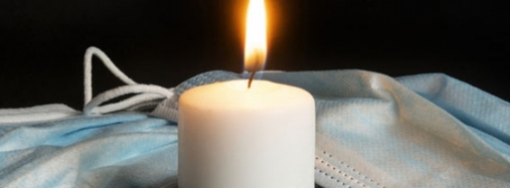 Una candela accesa circondata da mascherine chirurgiche