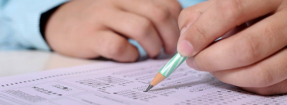 Una mano scrive su carta con una matita