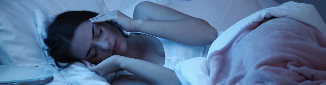 Una donna sdraiata a letto stringe la propria testa con le mani