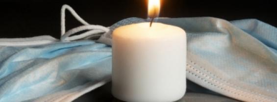 L'immagine mostra una candela intorno alla quale sono presenti delle mascherine, come simbolo della commemorazione delle vittime COVID-19.