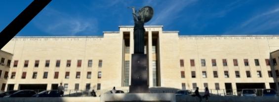 L'immagine mostra nello sfondo l'edificio del rettorato della Sapienza, e una striscia nera laterale per simboleggiare il lutto di questa grave perdita per la comunità accademica